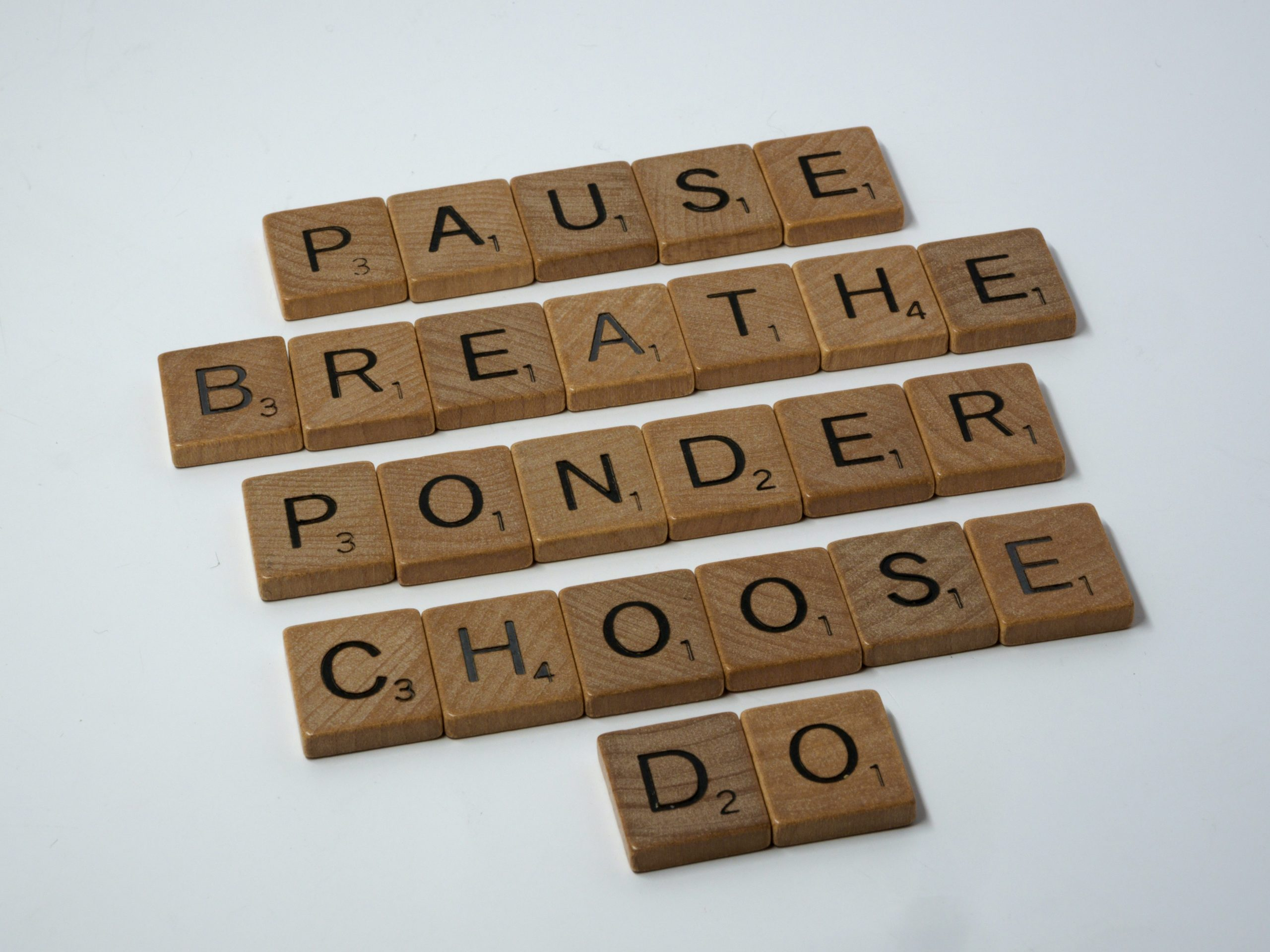 5 words spelled out in scrabble tiles: pause, breathe, ponder, choose, do
